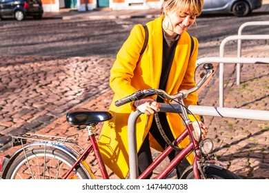 Young girl tethering bicycle on bicycle parking