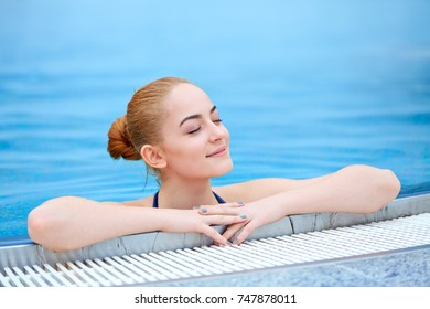 Young girl in a thermal pool at wintertime