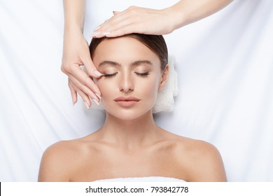 Young girl with thick eyebrows and perfect skin doing facial massage, beauty photo concept, hands on face, skin care, spa procedure, relax, white background.