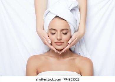 Junge Mädchen mit dicken Augenbrauen und perfekte Haut auf weißem Hintergrund, Handtuch auf Kopf, Beauty-Foto-Konzept, Hautpflege, Spa-Konzept, Behandlung, Gesichtsmassage.