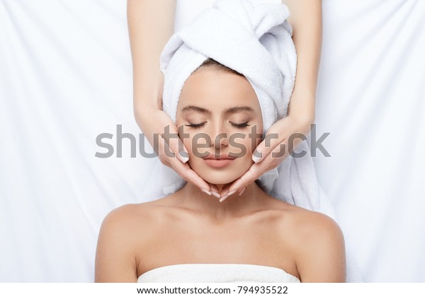 Young  girl with thick eyebrows and perfect skin at white background, towel on head, beauty photo concept, skin care, spa concept, treatment, facial massage.
