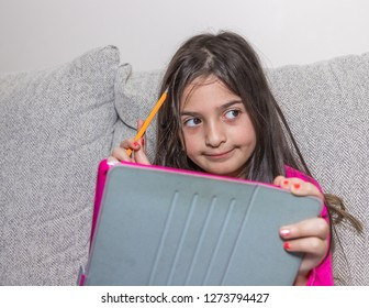 A young girl thinking while playing with her tablet