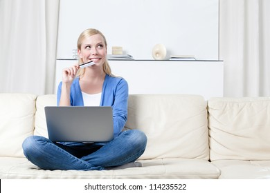 Young girl thinks about purchasing through the internet sitting on the sofa