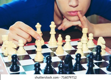 A young girl thinks over a chess combination indoors. Playing chess, board games.
