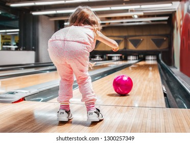 Young girl throwing a ball in bowling club. View from behind.
