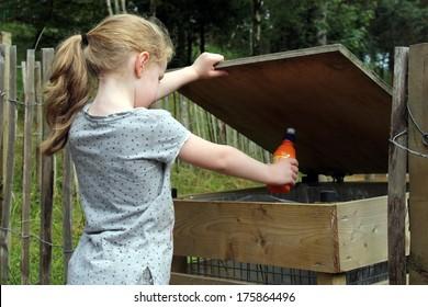 Young girl throwing trash into litter bin