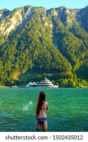 young girl throwing water in lake Achensee