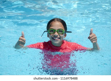 young girl with thumbs up in swimming pool summer fun