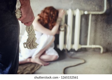 Young girl tied up on the floor. The abducted girl. The victim of violence sits on floor with tied hands. Domestic violence.