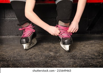 A Young Girl Ties Her Ice Hockey Skates in the Change Room of the Rink