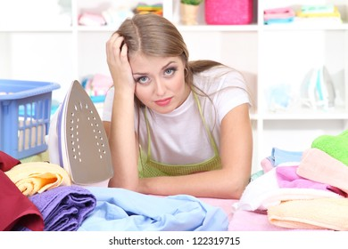 Young girl tired ironing in room
