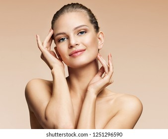 Young girl touching her face. Photo of girl with perfect skin on beige background. Youth and Beauty