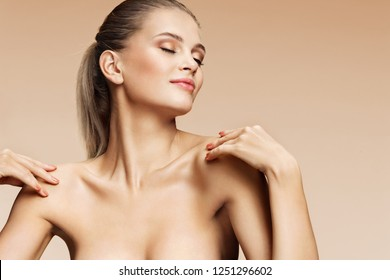 Young girl touching her healthy skin on beige background. Youth and skin care concept