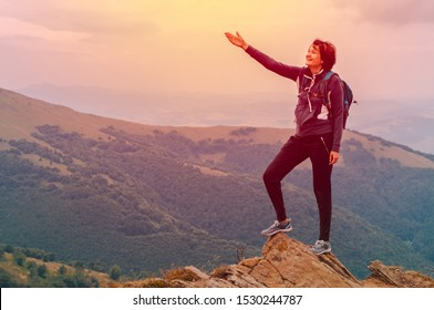 Young girl tourist with  backpack behind her stands on top of the mountain and enjoys a view of the Carpathian mountains at sunrise.