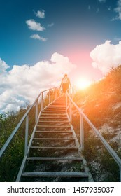 Young girl tourist climbs or goes up large steel staircase on mountain hill, summer travel adventure concept.