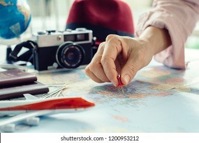 The young girl tourist planning vacation with the help of world map with other travel accessories around, travel concept.