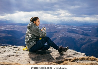 young girl tourist sits on a background of high mountains