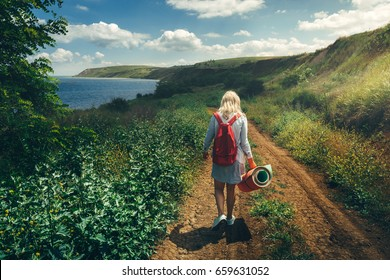 Young Girl Tourist, View From Behind, Walking Along The Road Towards The Sea Concept of Hiking and Adventure