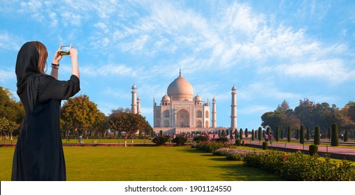 Young girl in traditional black  clothes  with take a selfie while Panoramic view of Taj Mahal - Agra , Uttar Pradesh, India