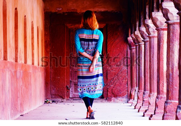 Young girl in traditional indian clothes in the hallway with columns near the West Gate. Taj Mahal, Agra, India.. Red stone.