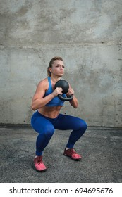 Young girl in training doing squats with weights.