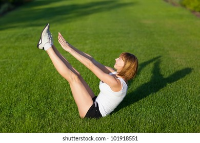 Young girl training at the park. Abdominal prelum exercise.