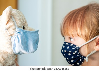 Young girl training to use a face mask during the pandemic -Focus on the teddy.