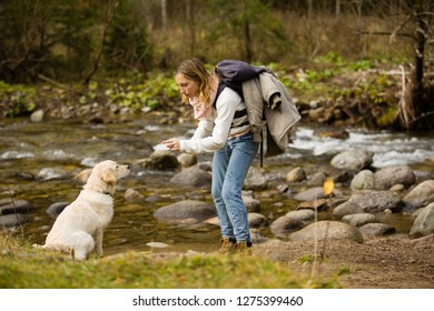 Young girl trains and plays with puppy golden retriever in the wild, next to a river.