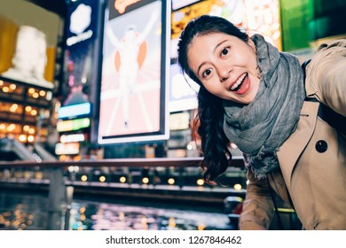 young girl traveler face camera smiling joyfully. female asian tourist taking selfie with the lighted advertisement board at dark night cheerfully. teeming osaka city urban night lifestyle concept.