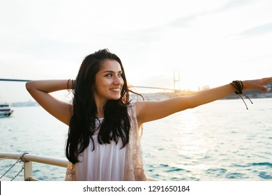 Young girl traveler relaxes while cruising on a yacht, looking at sunset and ocean, bridge on background. Bridge over the Bosphorus in the city of Istanbul