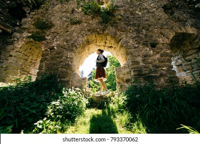 young girl traveler, standing in an ancient abandoned building surrounded by greenery