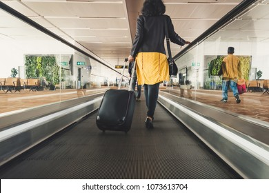 Young girl traveler walking with carrying hold suitcase in the airport. Tourist Concept. escalator, interior of the Indian pudong airport.