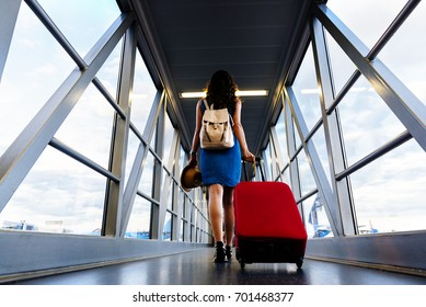 Young girl traveler walking with carrying hold suitcase in the airport. Tourist Concept.