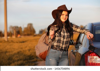 A young girl is traveling around the city hitchhiking. A beautiful young girl went on vacation. A female student in a cowboy hat on the road.