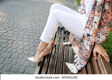 Young girl in trendy colorful cardigan sitting on the wooden bench in the park. Woman in a pink cape in high heels leather shoes.