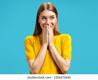 Young girl tries to stop giggling and look aside with her hands over her mouth. Photo of attractive girl in yellow sweater on blue background