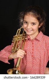 Young girl with a trumpet on a dark background
