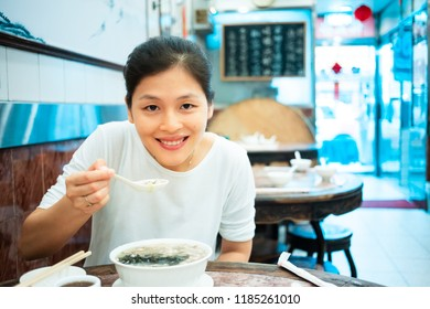 Young girl try out congee in traditional Chinese restaurant
