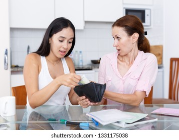 Young girl trying to ask money from an angry mom in kithen