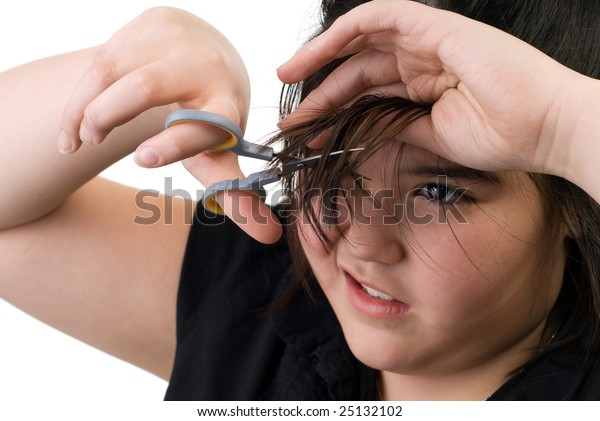 A young girl trying to cut her own hair with a pair of scissors, isolated against a white background