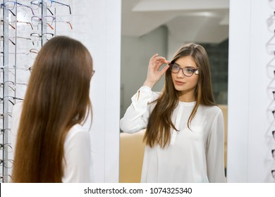 Young girl trying on eyeglasses in front of mirror. Helping to improve vision, saving eye health. Wearing white blouse. Standing near transparent stand with optical lenses.