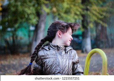 A young girl, twisting her head and waving her hair in the open air, a girl of 10 years turns her head in different directions. Long braid. Child having fun on the street.