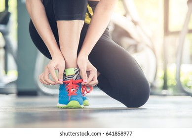 Young girl tying shoelace in the gym