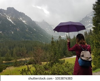 Young girl with umbrella in rainy day in mountains Tatry, Poland