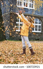 Young girl under falling autumn leaves