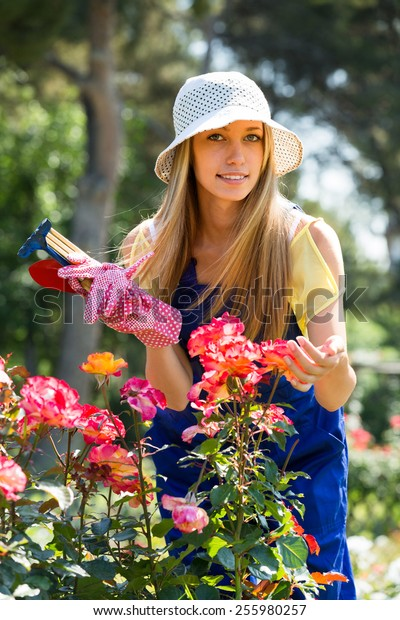 Young girl in uniform working with roses in garden