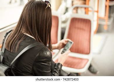 Young girl uses a mobile phone in the city bus. Technology cell phone isolation. Internet and social media