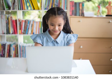 Young girl using computer at elementary school. Happy female child learning to use internet in a computer room.