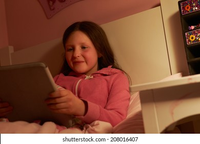 Young Girl Using Digital Tablet In Bed At Night