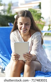 Young girl using digital tablet while relaxing by swimming pool on vacation